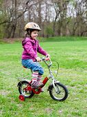 foto of four-wheel drive  - little girl learning to ride a bicycle with training wheels - JPG