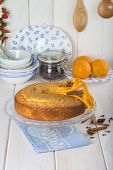 picture of sponge-cake  - Homemade orange sponge cake on a glass cake stand over the kitchen table - JPG
