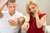 picture of handcuffed  - Portrait Of Unhappy Young Couple Handcuffed Together - JPG