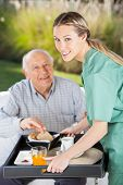 foto of nursing  - Portrait of smiling female nurse serving breakfast to senior man in nursing home - JPG