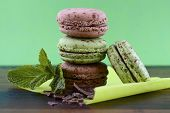 foto of mint-green  - Chocolate and mint flavor macaroons on dark wood table and green background - JPG