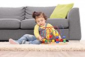 pic of girl toy  - Cute little girl playing with a toy seated on the floor isolated on white background - JPG