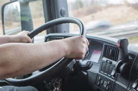 stock photo of steers  - Closeup view of the hands of truck driver who is holding the steering wheel - JPG