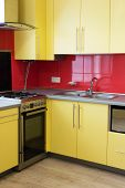picture of laminate  - yellow kitchen with cupboards with hinged doors topped with a grey worktops and fitted with appliances including microwave oven extractor hood a wall with a red tile and floor with soft sand grey laminate - JPG