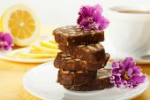 picture of violets  - Pile of delicious chocolate cake slices with the cookies filling decorated violet flowers on a white plate with lemon and cup of tea - JPG