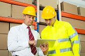 stock photo of warehouse  - Warehouse Worker And Manager Looking At Laptop In A Large Warehouse - JPG