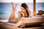 stock photo of woman bikini  - Smiling beautiful woman sunbathing in a bikini on a beach at tropical travel resort - JPG