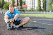 picture of stretch  - Handsome athlete is sitting on the road - JPG