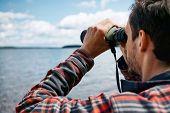 stock photo of binoculars  - Close up back portrait man looks through binoculars while fishing at the lake on vacation - JPG