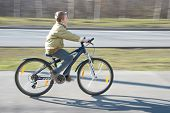 foto of ten years old  - Ten years old boy rides bike on bicycle path in springtime - JPG