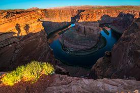 stock photo of horseshoe  - Shadows of couple taking pictures Horseshoe Bend Page Arizona at Sunrise - JPG