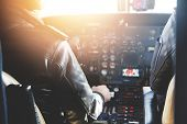 Two Unrecognizable Jet Airliner Pilots Wearing Leather Jackets Piloting Aircraft At Sunset, Sitting poster