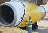maintenance worker attending to a jet engine