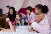 stock photo of slumber party  - Five adorable girl friends talking and laughing at a slumber party - JPG