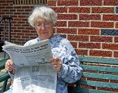 picture of senior-citizen  - senior woman reading newspaper on outdoor bench - JPG