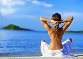 stock photo of woman beach  - woman on the beach near the sea meditating - JPG