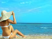 stock photo of sunbathing woman  - Woman in hat sitting on the beach - JPG
