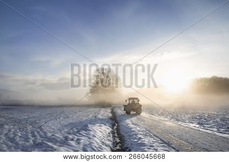 Tractor Silhouette On A Snowy