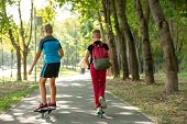 Happy Boys With Roller Skates And Scooter, Walking On The Road At The Park, Summertime poster