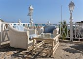 Two cane armchairs and a table on the terrace against Atlantic. Tenerife island, Canaries