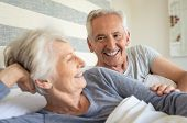 Smiling senior couple lying on bed on a bright sunny morning. Happy old man lay near his wife in bed poster
