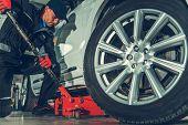 Caucasian Automotive Mechanic With Floor Jack Car Lift. Vehicle Maintenance In The Auto Service Cent poster