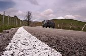 selective focus of white roadside on background blurred car