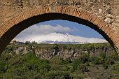 view  of volcano etna framed by blurred arch