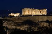 view from Filopappos-Philopappos hill of Acropolis and Parthenon by night in the city of Athens