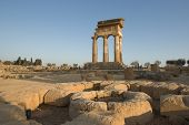 doric temple Of Castor and Pollux in the Valley Of Temples in Agrigento, on foreground circular altar stone