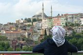 a musulman woman is wearing religious veil and is looking at a Istanbul cityscape with a mosque