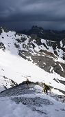 Backcountry Skiers And Mountain Climbers Retreat Down From A Steep Mountain Peak Over Rock And Snow  poster