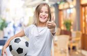 Young beautiful girl holding soccer football ball over isolated background happy with big smile doin poster