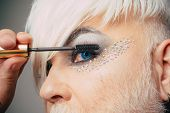 Adding Length And Volume. Fashion Male Eye Makeup. Transgender Man Apply Mascara. Transgender Man We poster