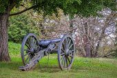 A Long Silent Civil War Cannon Sits In A Virginia Field. poster