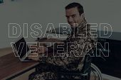 Military Veteran. Disabled Man In A Wheelchair. Man Sitting At Table. Man Using Laptop. Man Is Soldi poster