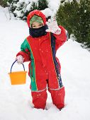 Child playing in the snow with snow