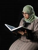 Muslim woman is reading a holy quran