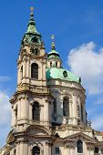 Steeple and clock tower of St. Nicholas Cathedral in Prague, Czech Republic.