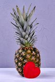 Whole Green Pineapple And Red Heart. Fresh Organic Ananas On Light Wooden Background. Food And Love. poster