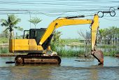 A Hydraulic Excavator Operates In A Flooded Road.
