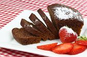 one cut chocolate cake on a white plate with some strawberries