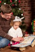 Little girl with her dad near Christmas tree