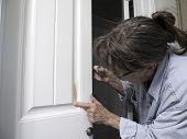 Woman Painter Puttying Closet Door To Remove Bump In Door. poster