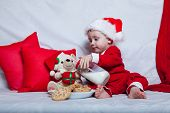 A Little Kid In A Red Cap Eats A Cookies And Milk. Christmas Photography Of A Baby In A Red Cap. New poster