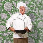 Male Chef Stirring A Non Stick Pan On Wallpaper