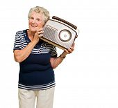 Porträt von Senior Woman hören Musik aus Radio Isolated Over White Background