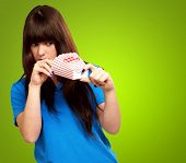girl looking through empty popcorn packet isolated on green background