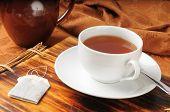 foto of darjeeling  - A cup of hot Darjeeling Tea near a teapot - JPG