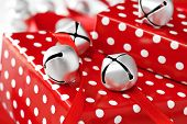 Silver jingle bells with red satin ribbon on gifts wrapped in fun polka dot paper.  Macro with shall